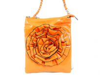 Crossbody bag has a top zipper closure, a detachable strap and a large flower detail. Made of faux leather.