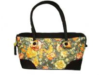 Double strapped fashion bag embellished with a beautiful flower design and a top zipper closure.