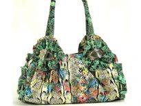 Designer Inspired Multi Color Snake Print PVC Handbag with big ring accents on the sides of the bag. Double handle with zipper closure & solid color gathered accents on the start of the straps.