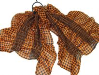 This checkered print orange & black 100% polyester scarf can be a perfect accessory all year round. The scarf is stretched in the middle with a striped pattern & gives a ruffled look. Imported.