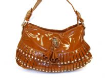 Fashion shoulder bag has a top zipper closure, a single strap and layered frilla with stud details on them. Made of PVC.