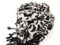 This 100% wool scarf in ivory color has artistic abstract figures print on it in black color. Has twisted fringes at its edges. Imported. Dry clean only.