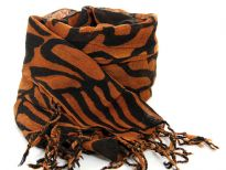Abstract artistic lines travel over this two-tone rich colored scarf in rust & black colors tipped with twisted fringe. 100% wool scarf; imported. Dry clean only.