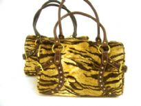 Tiger Pattern Faux Fur fashion handbag has a studded trim in the front, a double handle and a top zipper closure. Belt accents on the sides of the bag.