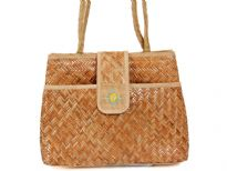 Straw and jute shoulder bag made with double shoulder straps and a front flap magnet closure.