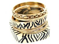 Tribal inspired design ivory wooden & metal bangle with black painted lines. 4 gold tone bangles with each having its own etched design or is plain & simple. Funky looking set can give an edge to any kind of outfit.