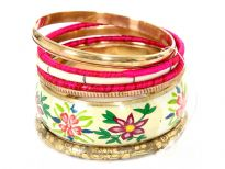 Multi colored floral print on ivory wide cuff bangle makes this 7 piece fashion bangles set unique & attractive. 5 thin bangles are in gold, fuchsia, ivory colors in different designs/material and also a gold bangle with etched design on it.