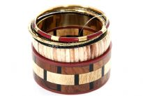 Cherry & wood colored wide cuff bangle with beige color patterned resin bangle comprises this six piece bangles set. Two thin black resin bangles, one cherry/gold colored & one gold colored metal bangle are the other bangles in this set. Imported.