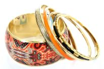 Exotic print in orange & black colors decorate the wide cuff gold colored bangle in this six piece bangles set. Five other bangles comprises of one orange, one black resin bangle & three gold colored metal bangles in different designs/width. Imported.