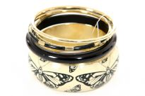 This exotic five pieces bangles set has one wide cuff butterfly print resin bangle, one thick & one thin black resin bangle and two gold colored metal bangles. Imported.