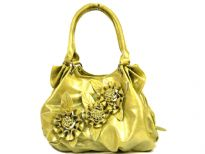 Fashion Handbag in Shining PVC Material with top zipper closure and double shoulder handle. Same color triple flower appliques in the front. Belt like accents on the sides of the bag.