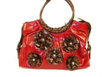 PVC Flower Handbag with round double handle & belt accents on the sides of the bag. Floral patchwork in contrasting color makes the bag very trendy & fashionable.