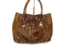 Designer Inspired Handbag with drawstring closure and a double handle has flowered applique details and ruches at bottom. Made of PU (polyurethane).