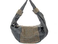 Faux Leather Studded Shoulder bag. This one piece bag has golden studs in the middle of the bag as well as on single shoulder strap. Top zipper closure.