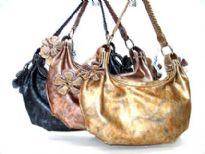 Washed look Polyutherene handbag with braided shoulder strap and hanging floral accents.