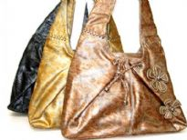 Washed look two tone hobo bag with top zipper closure, single shoulder strap and floral accents. Made of faux leather.