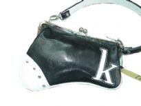 Asymmetric handbag has a detachable single strap, a framed kiss lock closure, and letter detail at corner. Made of faux leather.