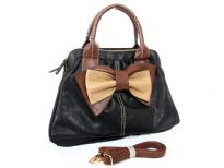 Bow accent dual compartment fashion handbag. Adjustable shoulder strap included. Back zipper pocket.
