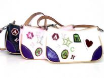 PVC Fashion Handbag has a single strap, a top zipper closure and embellished letters and shapes. Made of faux leather.