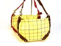 Plaid print in multi colors fashion bag with belt like accents in contrast color bordering the bag. Top zipper closure and a detachable single strap. Made of PVC.