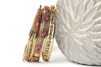 Antique gold colored 8 pieces fashion bangles set has fuchsia beads on 2 of the bangles which gives an edge to this set. 5 thin bangles with 2 bangles have metal floral pattern & one wide bangle has fuchsia stones. Hand crafted in India by expert artisans.