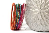Colorful & lightweight 12 pieces bangles set can be matched with any kind of outfit. 9 thin glittery bangles, one thin beaded bangle & 2 threaded bangles - one fuchsia/blue & one orange/multi colored. Hand crafted in India.