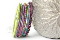 Colorful & lightweight 12 pieces bangles set can be matched with any kind of outfit. 9 thin glittery bangles, one thin beaded bangle & 2 threaded bangles - one lime green & one multi colored. Hand crafted in India.