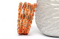 This Orange Beads Gold Metal Fashion Bangles Set can add zing to nay kind of outfit. Set includes 4 thin bangles, 2 petal patterned with beads and 3 bangles having beads in boxy shape. Durable & long lasting quality.