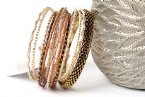 This set of fashionable bangles set includes 14 Pieces in different colors & patterns. Patterned gold colored metal wide bangle with 13 thin bangles which have glitter designs on them.