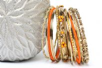 This 15 pieces set of fashion bangles includes one wide patterned bangle with orange beads on it, 2 orange bangles have fabric on it, 2 have metal pattern on it & rest have glitter.