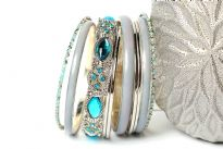 Chunky looking assortment of 10 pieces including 4 thin metal bangles, 3 periwinkle blue resin bangles, 2 thin  bangles with blue resin & one wide metal pattern bangle with turquoise rhinestones on it. This set can give funky look to any kind of outfit.