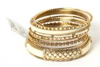 Gold Colored Metal Fashion Bangles Set consists of 8 pieces - one ivory colored wide bangle with metal mesh design, beaded thin bangles & patterned metal bangles also. Can be matched with any kind of outfit for that extra zing.