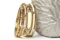 This Ivory with silver hand crafted fashion bangles set has 8 pieces - one broad resin bangle in mesh metal frame, one black resin bangle, 2 thin beaded bangles & 4 thin silver colored bangles. Matches with almost any kind of outfit & very durable.