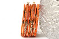 Bright colored elegant looking gold colored metal fashion bangles set of 12 pieces has small orange beads on 7 thin bangles, 3 thin gold colored bangles & 2 are resin bangles encrusted in patterned gold colored metal frame.