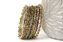 Gold colored Metal Fashion Bangles Set with Beads in Shades of Green. Bangles have a wavy pattern which is embellished with beads all around it. Sized to fit small to medium wrists.