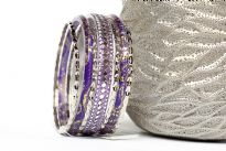 Shiny & Glittery seven piece set of fashion bangles in purple hues includes one wide bangle in Aluminium with mirrors design on it, 2 resin bangles with gold glitter inside them & 4 thin silver bangles. Hand crafted in India.