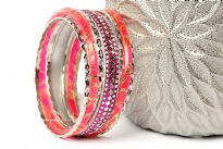 Shiny & Glittery seven piece set of fashion bangles in hot pink hues includes one wide Fuchsia bangle in Aluminium with mirrors design on it, 2 hot pink resin bangles with gold glitter inside them & 4 thin silver bangles. Hand crafted in India.