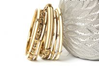 Beautiful Gold colored Metal Fashion Bangles Set can give that chic style to any kind of outfit at any time of the day. Set includes 3 thin gold bangles, 3 thin beaded bangles, 1 floral metal pattern bangle, 2 resin bangles in gold frame & one wide ivory resin bangle encrusted in gold frame.
