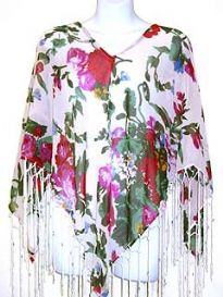 V-neck 100% rayon poncho top in white color with multi colored floral print. Hanging patterned fringes along its border. Imported.