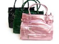 Croco Embossed shining patent leather spacious handbag with double handle, top zipper closure & belt like embellishments on the sides of the bag. Multiple zipper pockets in the front. Made of PU (polyurethane).