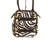 Designer Inspired Tote bag has a zebra print pattern and multiple zipper details. Bag has a top zipper closure and a short double handle. Made of faux leather.