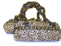 Round Shoulder Bag with animal print pattern has a double handle, top zipper closure and studded details. Made of PU (polyurethane)